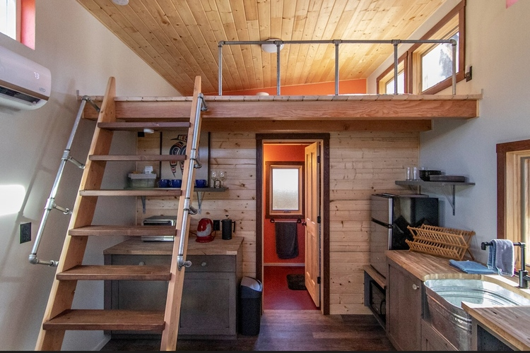 Photo of both the kitchen area, and also staircase up to the bedroom loft area.