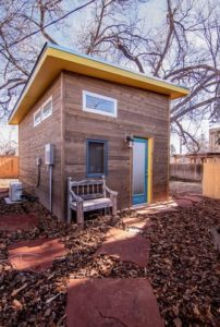Exterior view of the tiny house, including a bench at the front and utility supply into the side of the house.