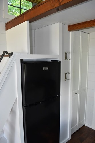 Apartment style fridge/freezer space, stairs going up to loft area and (closed) pantry door.