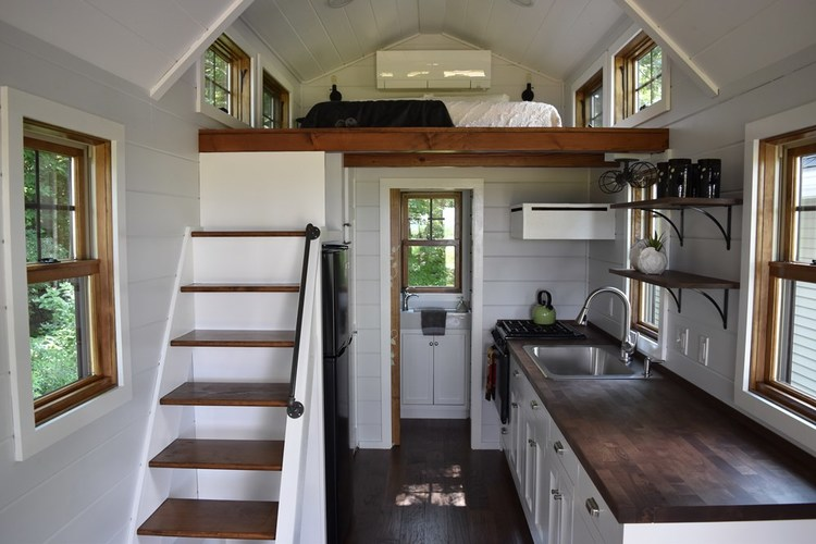 """alt=""""Overall view of the kitchen area, stairs up and upstairs loft bedroom area."""""""