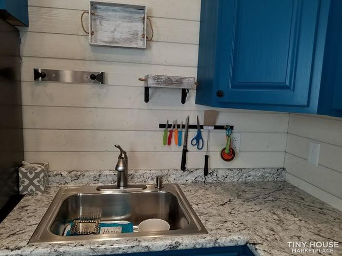 Close-up view of the kitchen sink area, along with the wall mounted storage options.