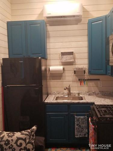 """alt=""""Wider view of the kitchen area with small fridge/freezer, wall cabinets and split unit."""""""