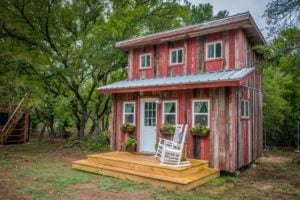 Outside of the Little Red Hen Cabin in Texas, showing a two-story tiny house and two-tier height wood front porch.