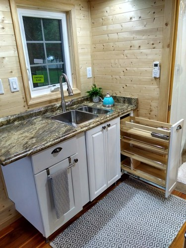 The kitchen area with pull-out storage being shown, and also the sink.