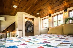 Timbercraft Tiny Homes' Denali gooseneck tiny house; a look at the master bedroom with a double bed and in-built storage via a wardrobe.