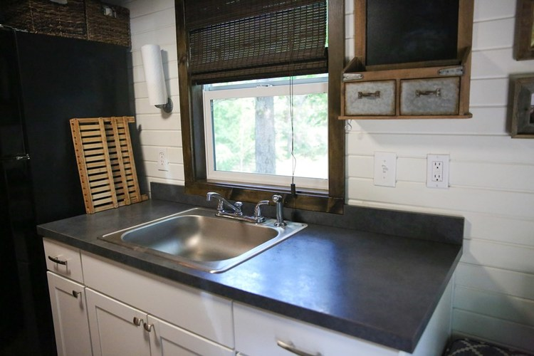 Kitchen worktop and sink, along with further wall mounted storage. Also has a window with views to the outside.