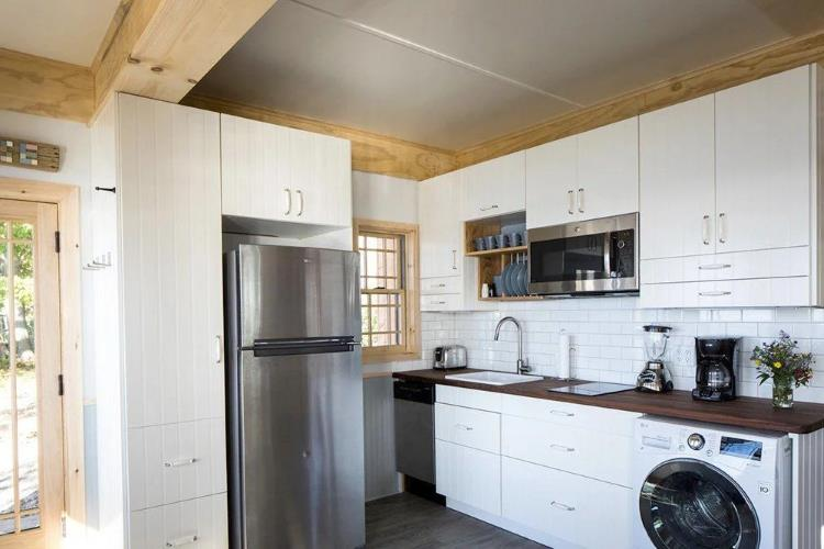 Woodland (in Nashville) tiny house's kitchen area, showing ample storage and a full size fridge/freezer and washer/dryer.